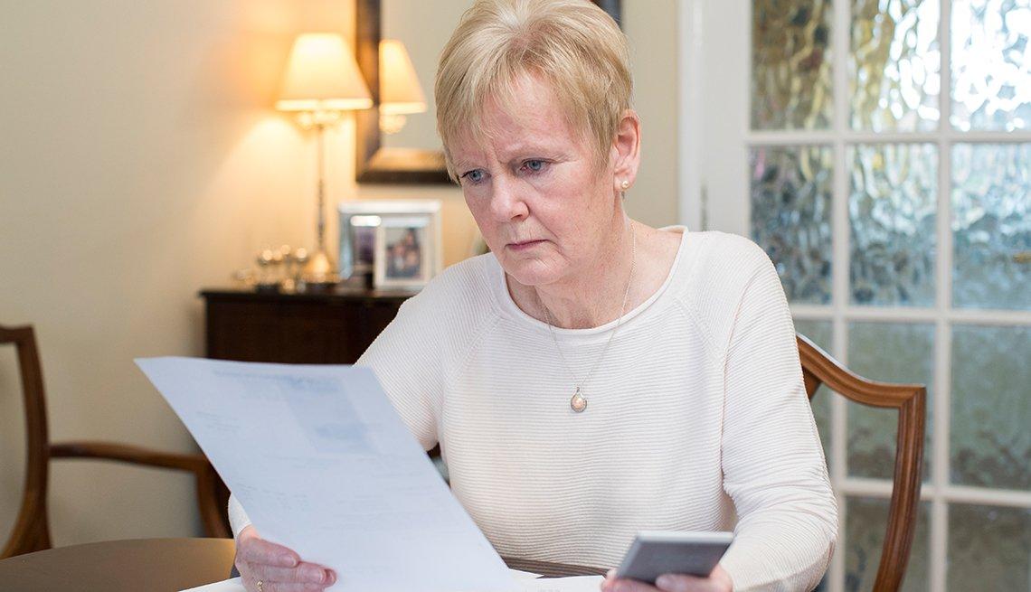 Mujer mirando un papel con cara preocupada