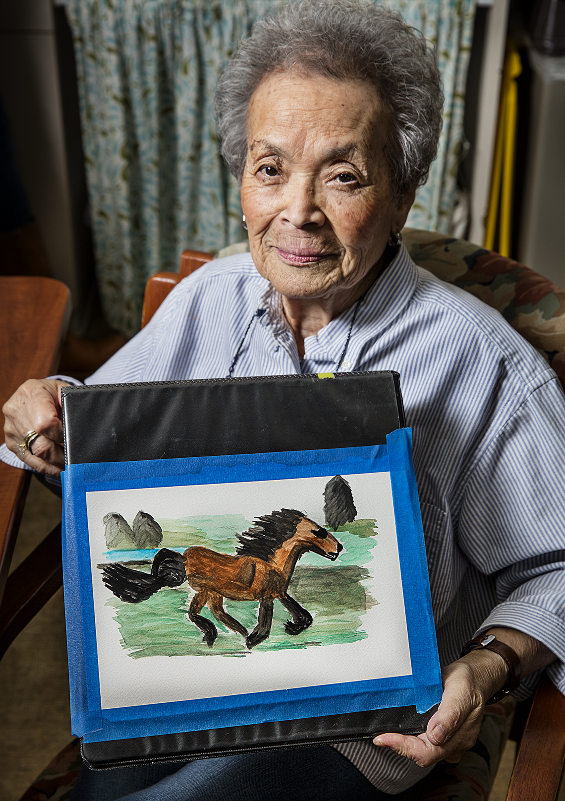 Mature woman holding a painting that she created of a horse.
