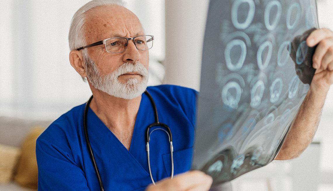 Un médico analiza unas radiografías del cerebro de un paciente