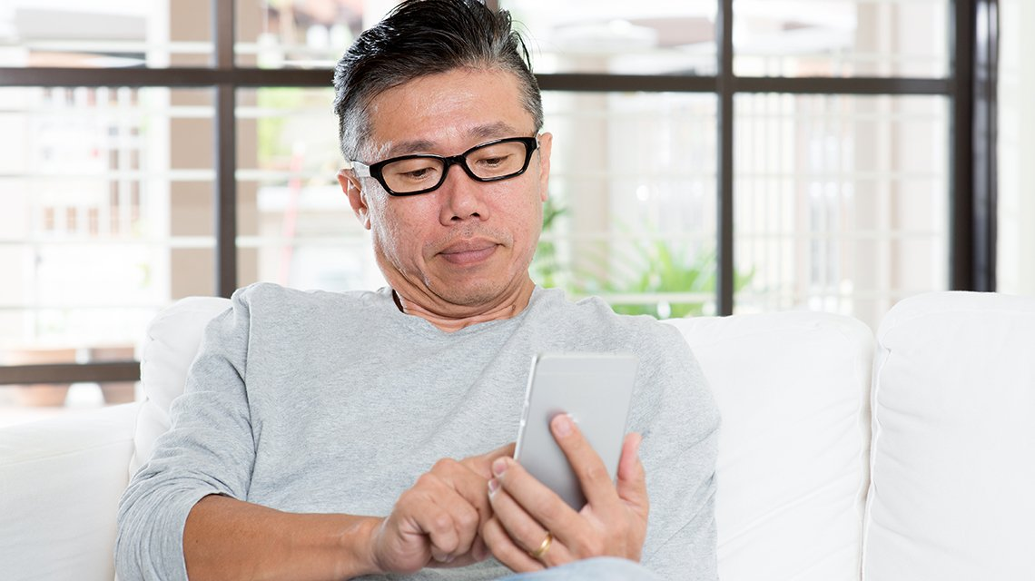 Portrait of mature man using smart phone, sitting on sofa at home.