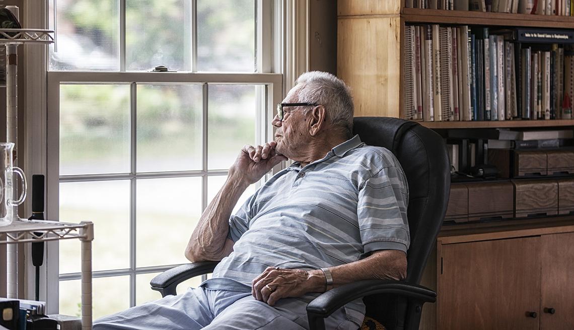 Un hombre mayor sentado en una silla mira por una ventana