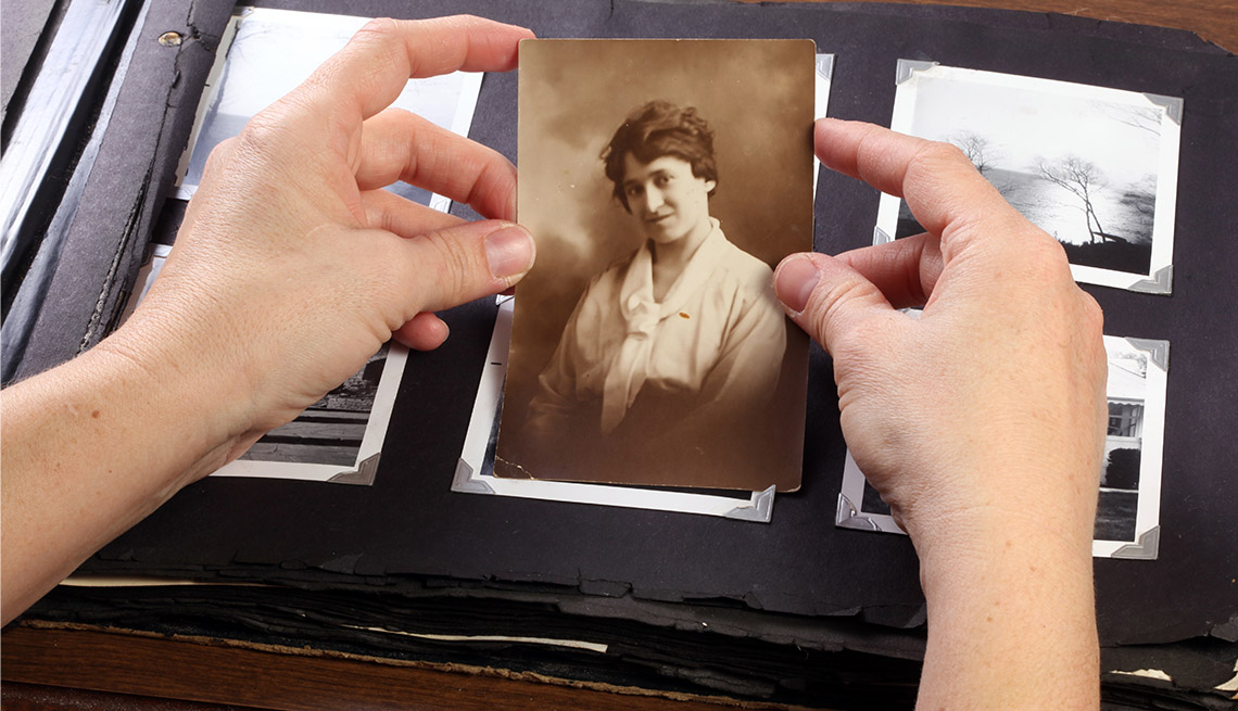 Person holding a photo from an album