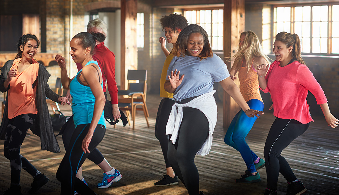 Group of young and middle aged women exercising and dancing in a gym.