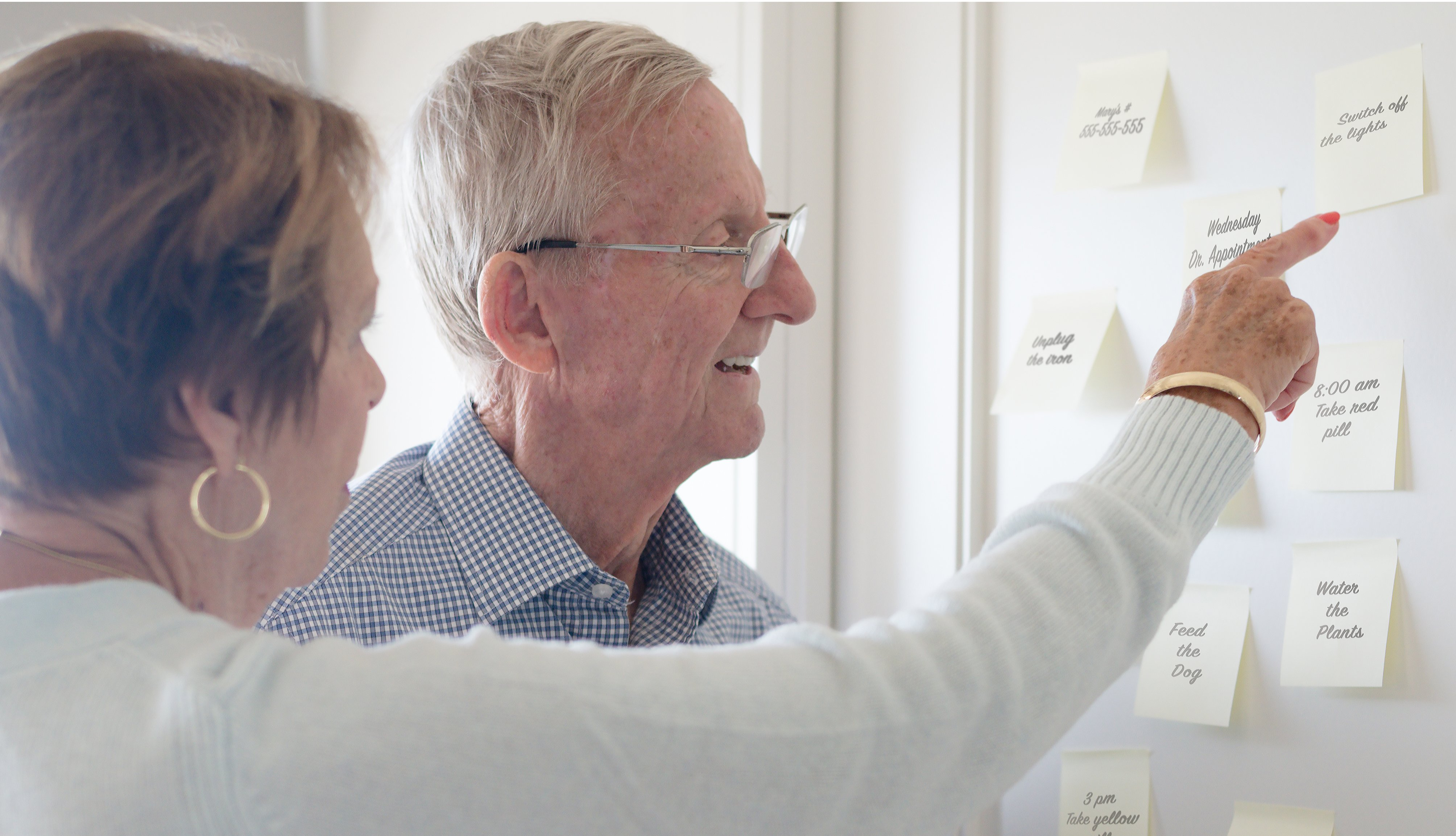 woman pointing out reminders on sticky notes to dementia patient