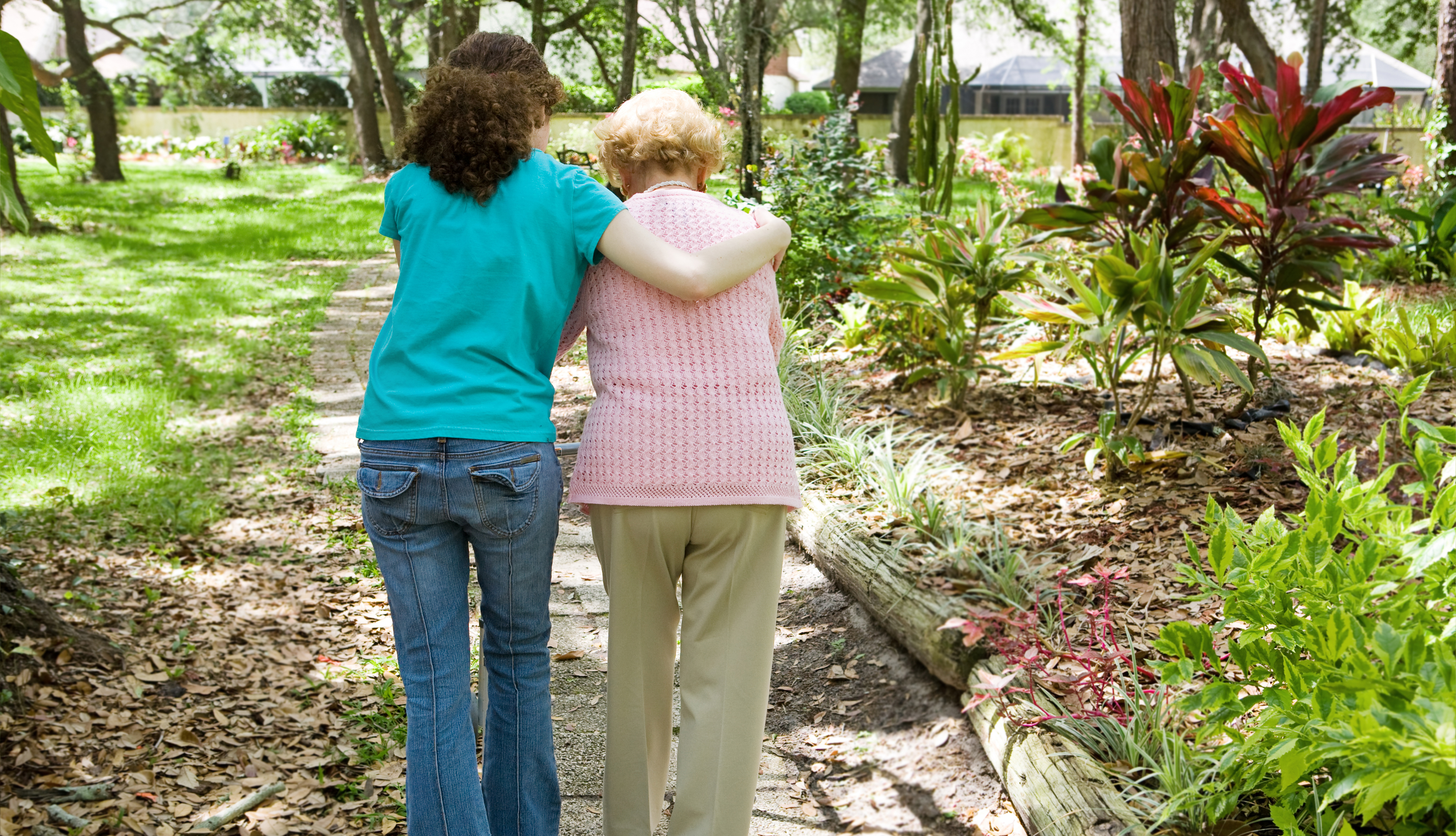 female caregiver walking on a path with an older woman, supporting her
