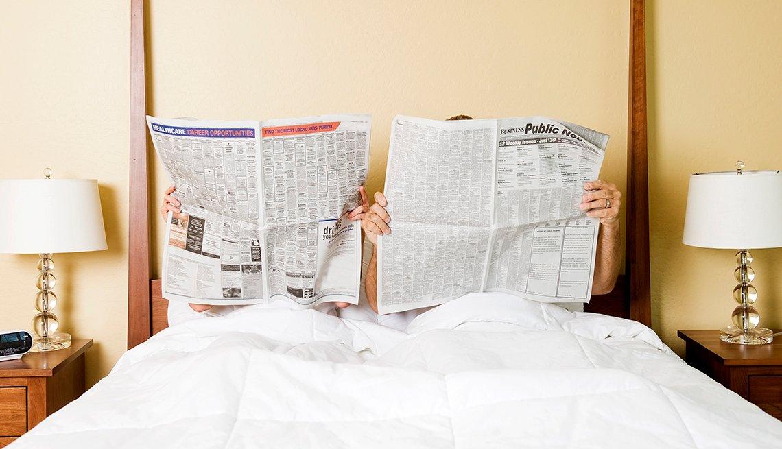 Pareja en la cama leyendo el periódico