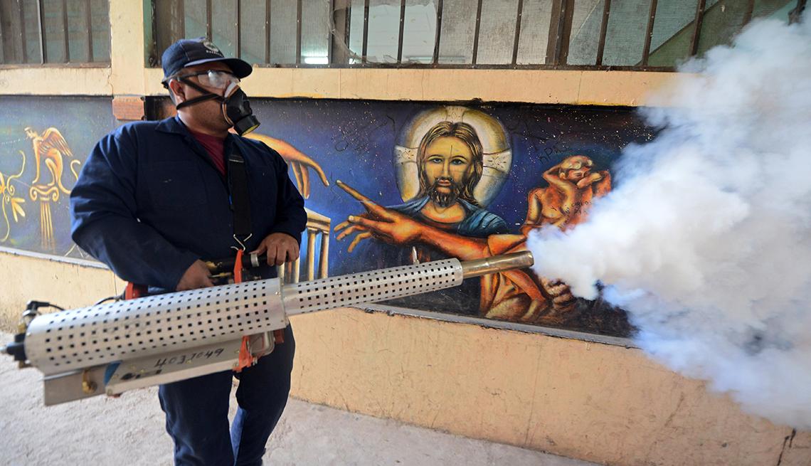Empleado fumigando en contra del dengue