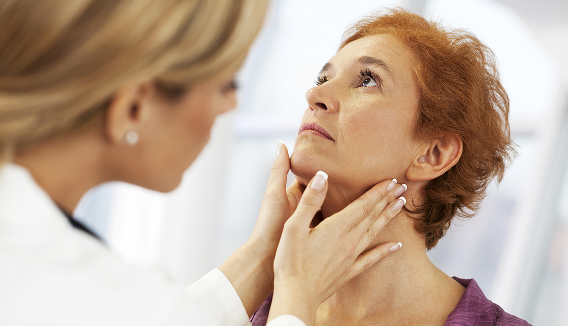 Doctora revisandole la tiroides a una paciente