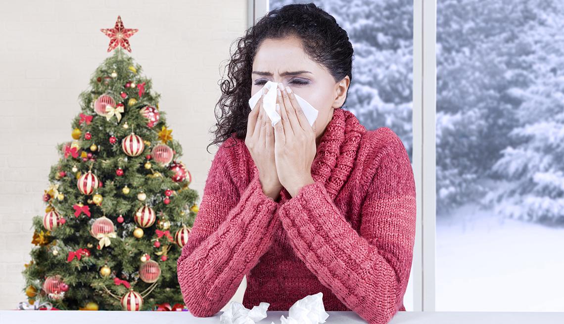 Mujer estornudando cerca de un árbol de Navidad.