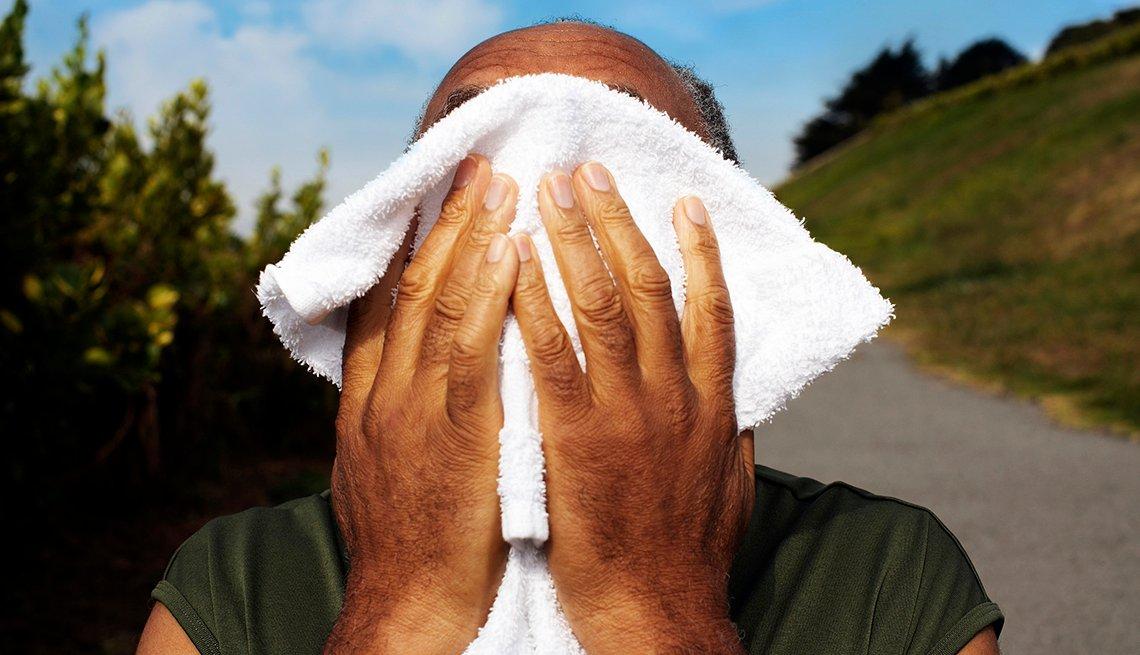 Hombre secándose el sudor con una toalla