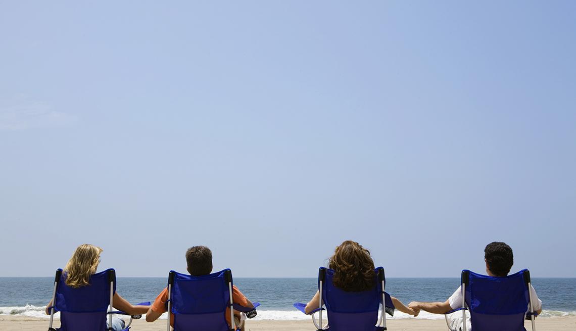 Cuatro personas sentadas en sillas azules frente al mar.