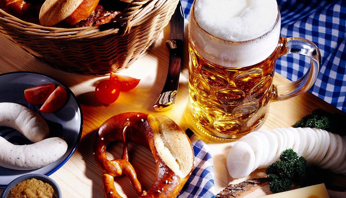 Jarra de cerveza con un pretzel, salchicha y otros alimentos procesados encima de una mesa.