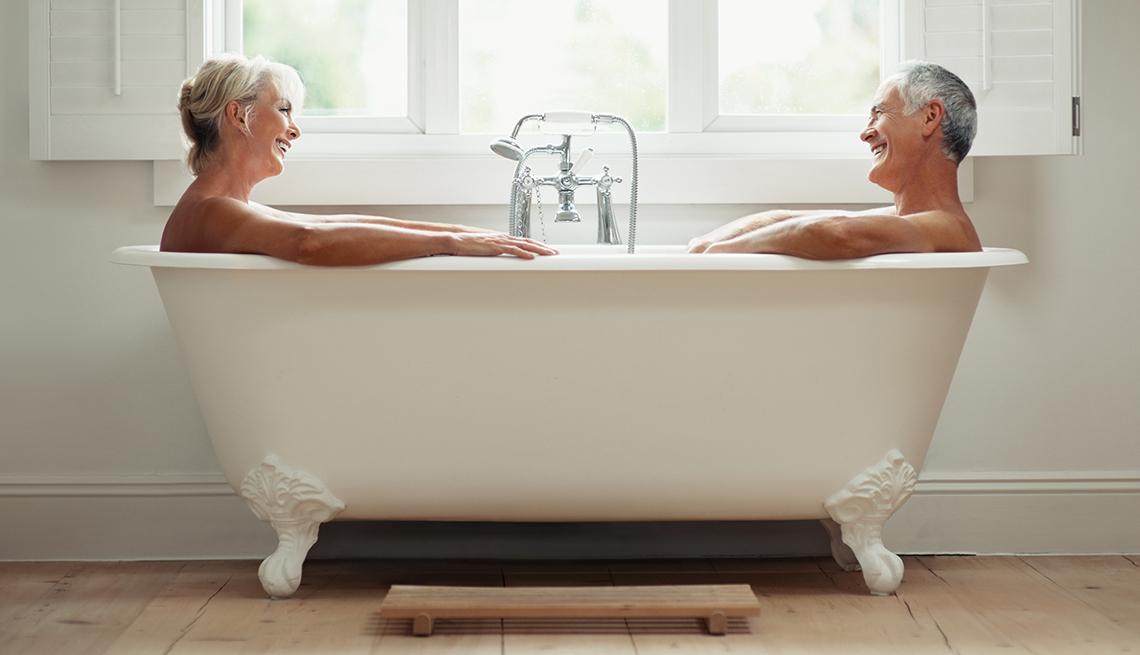 Hombre y mujer de mediana edad felices en una tina de baño.