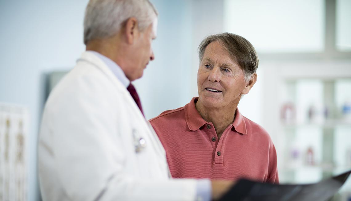 Doctor explica a paciente resultados de radiología.