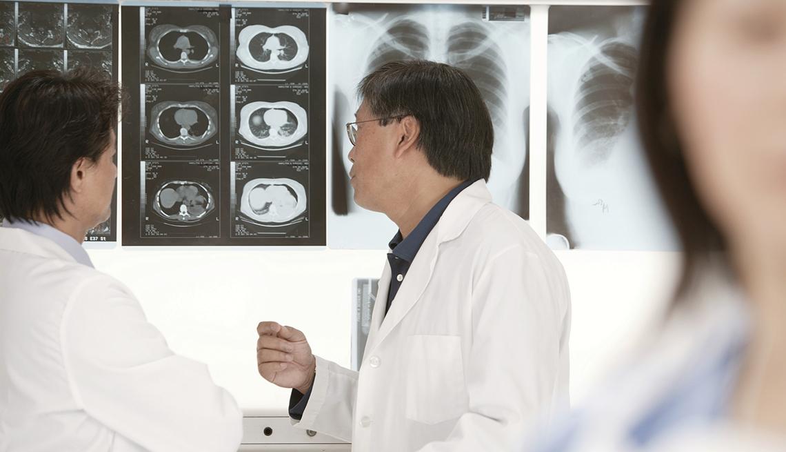 Médicos miran radiografías en una pantalla blanca.