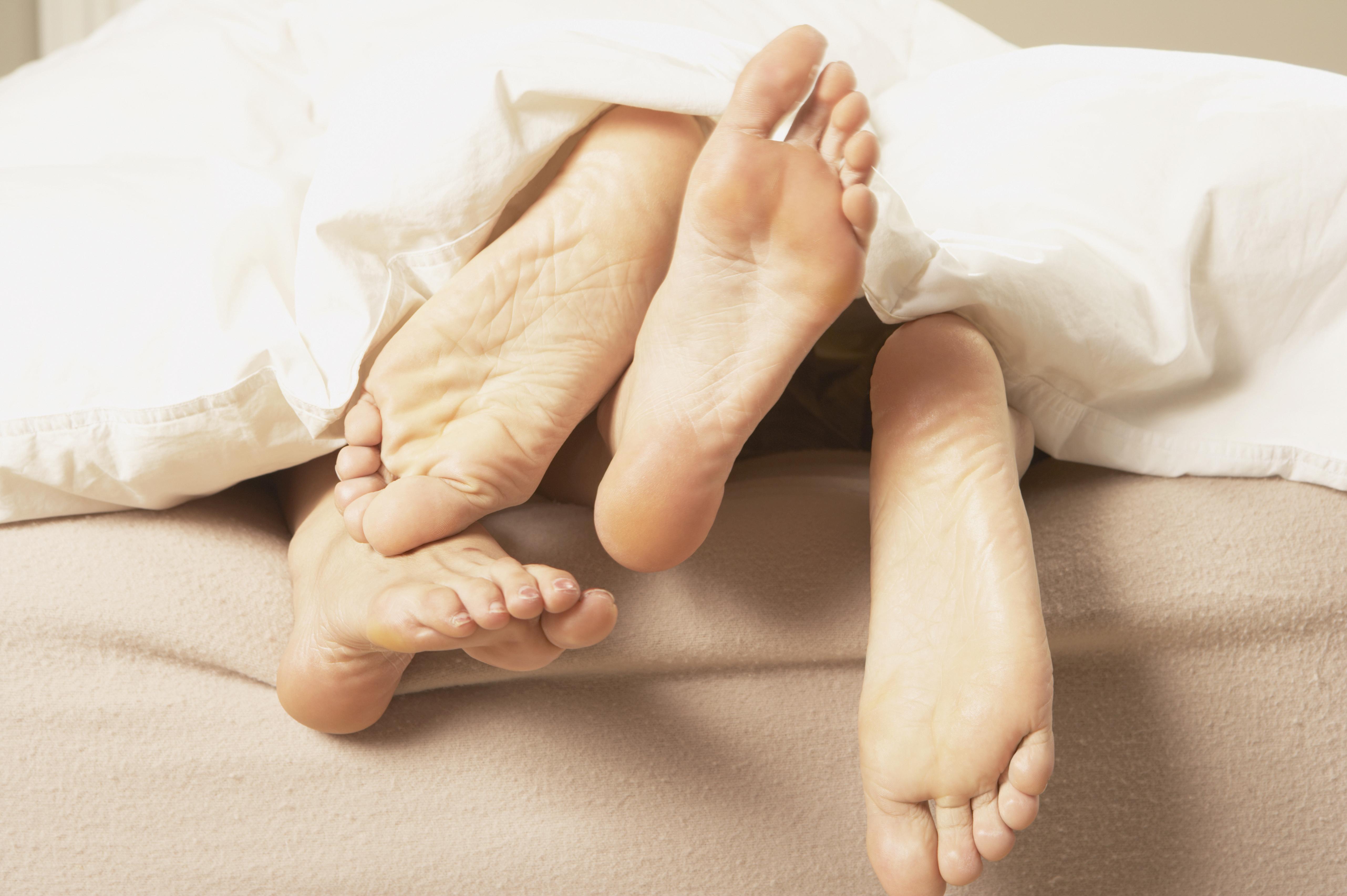 Pies de una pareja en la cama.