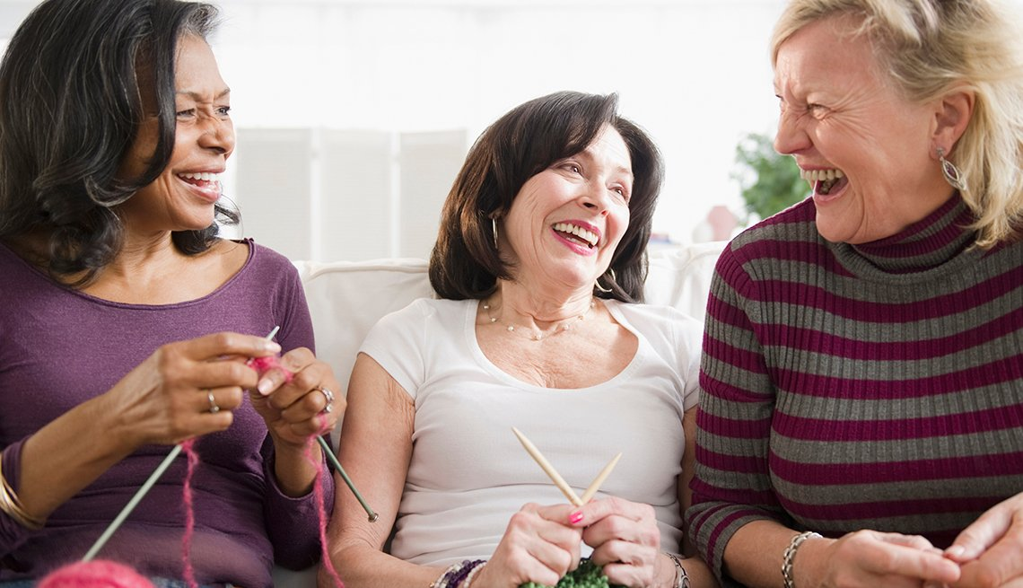 Tres mujeres se ríen mientras sostienen agujetas de tejer en sus manos.