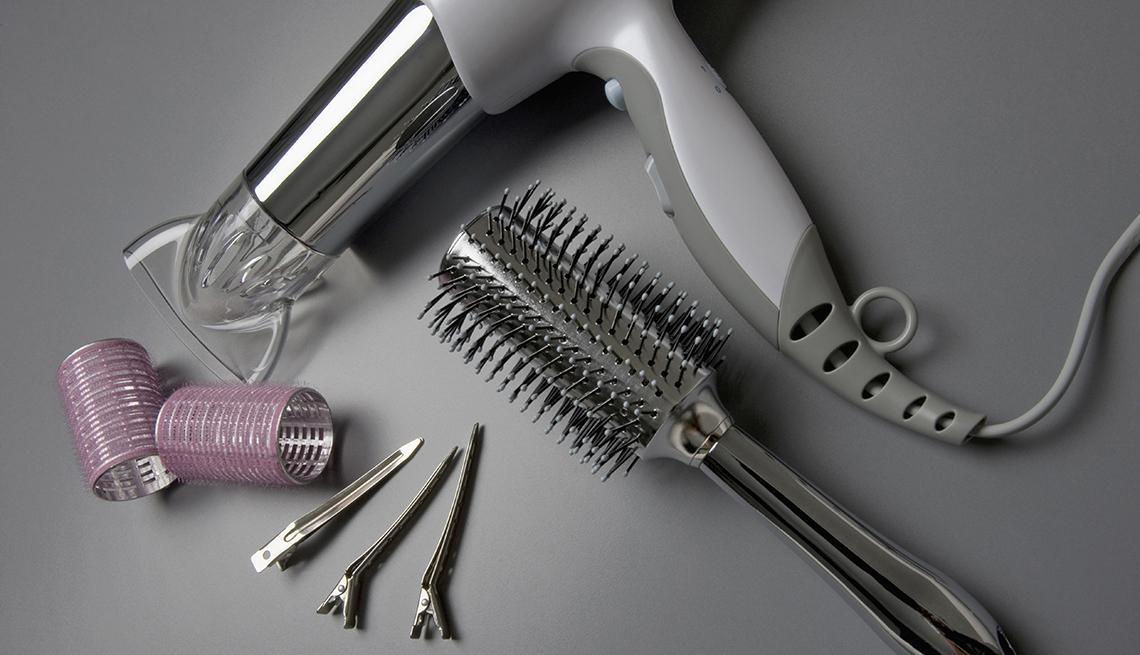 Secador de pelo colocado al lado de un cepillo de pelo, tres pinzas y dos rulos.