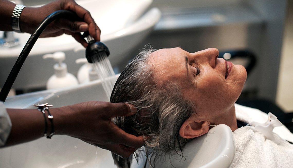 Mujer lava el cabello de mujer de mediana edad en una lavamanos en un salón de belleza.