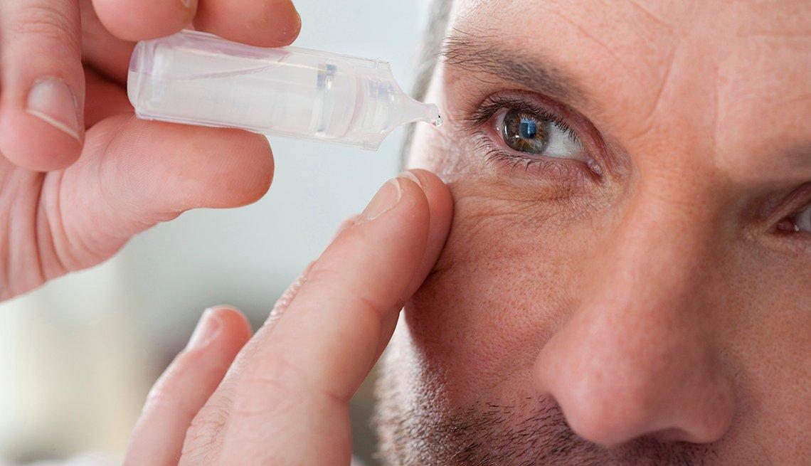 Hombre se aplica gotas en el ojo.