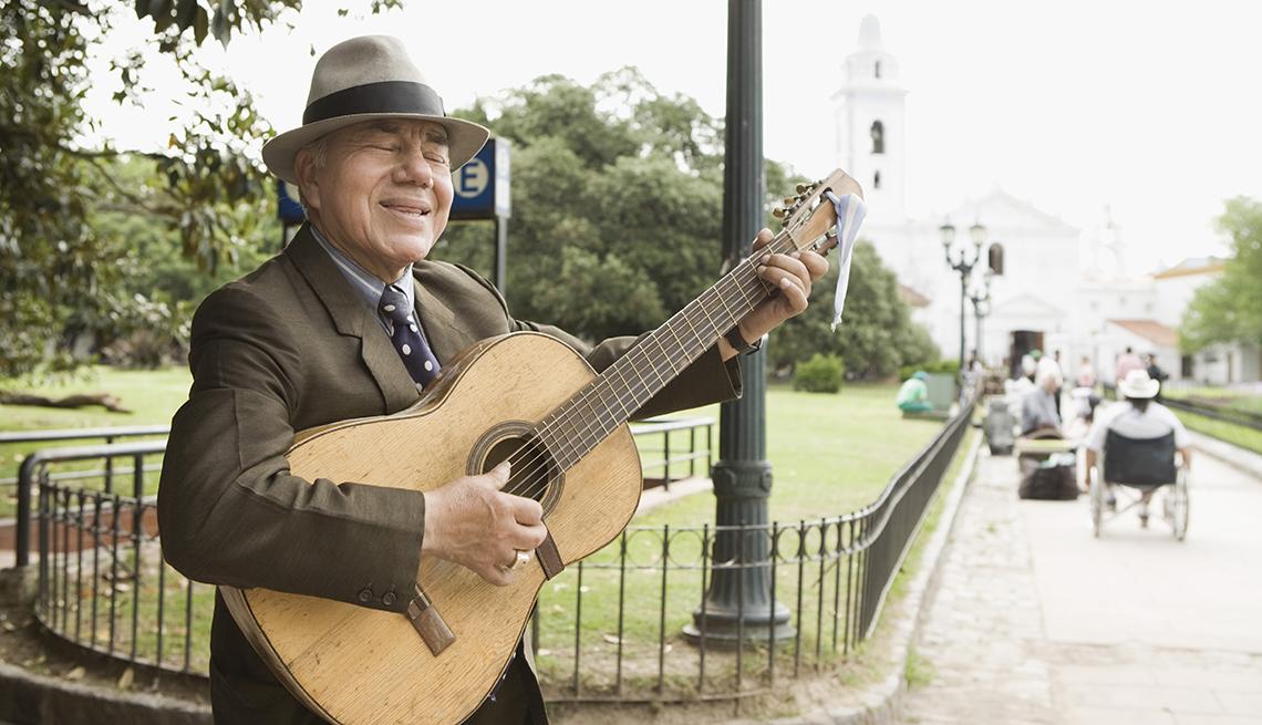 Hombre con sombrero y de traje con corbata toca la guitarra en una plaza pública.