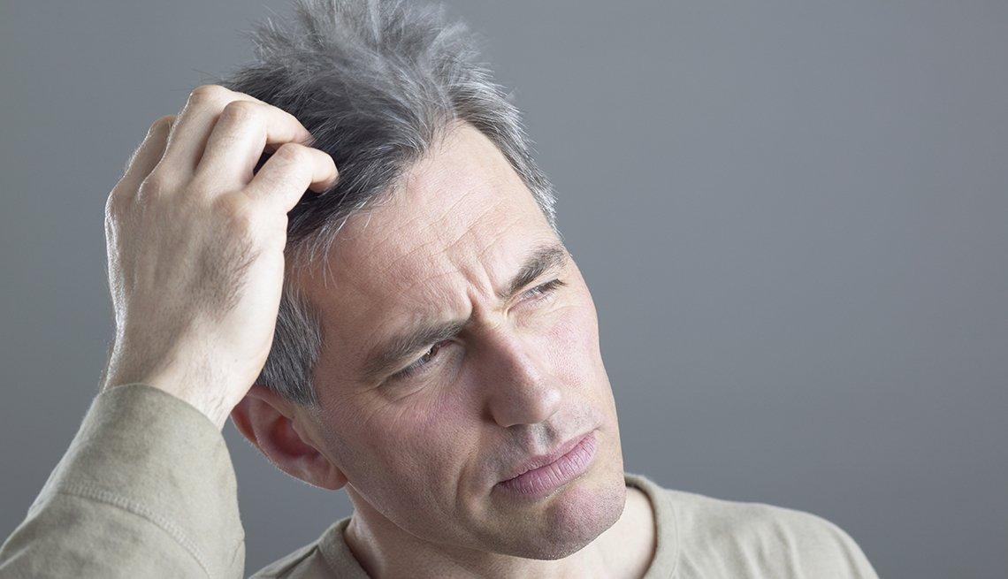 Hombre de mediana edad con las manos en su cabello.