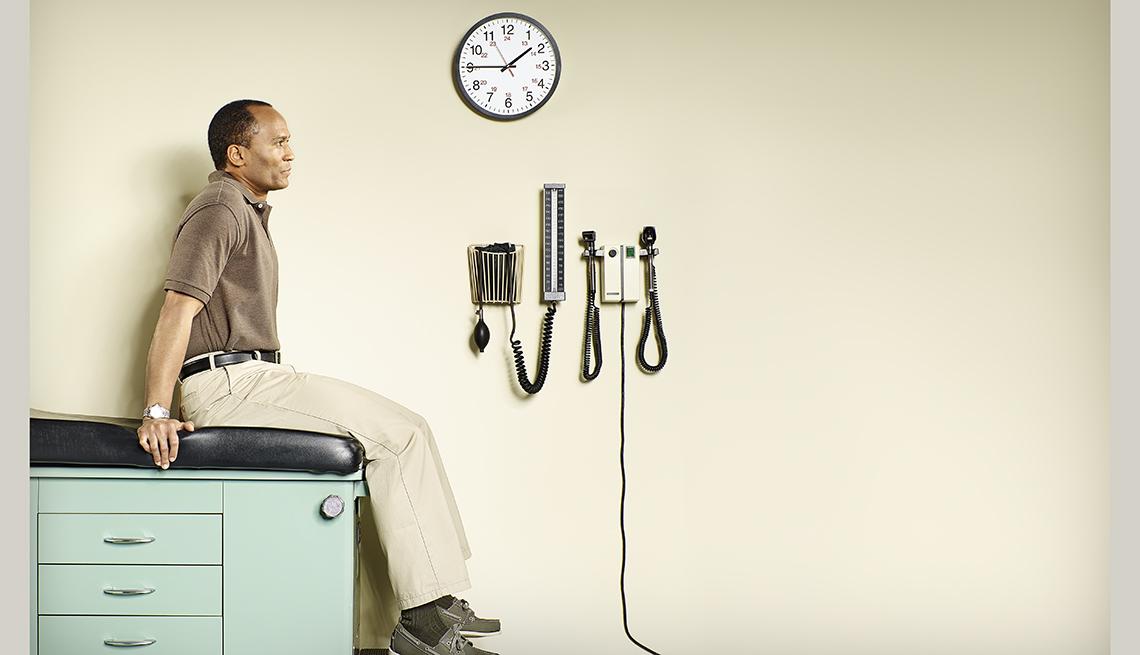 Hombre afro-americano sentado en una mesa en una consulta médica.
