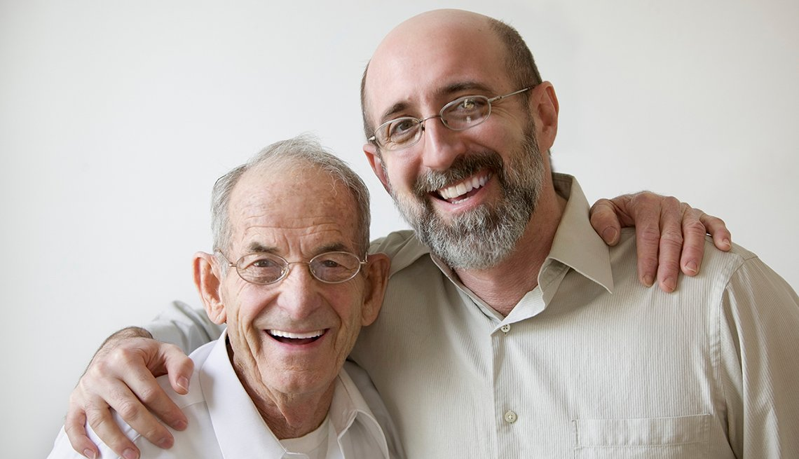 Padre e hijo abrazados sonríen a la cámara.