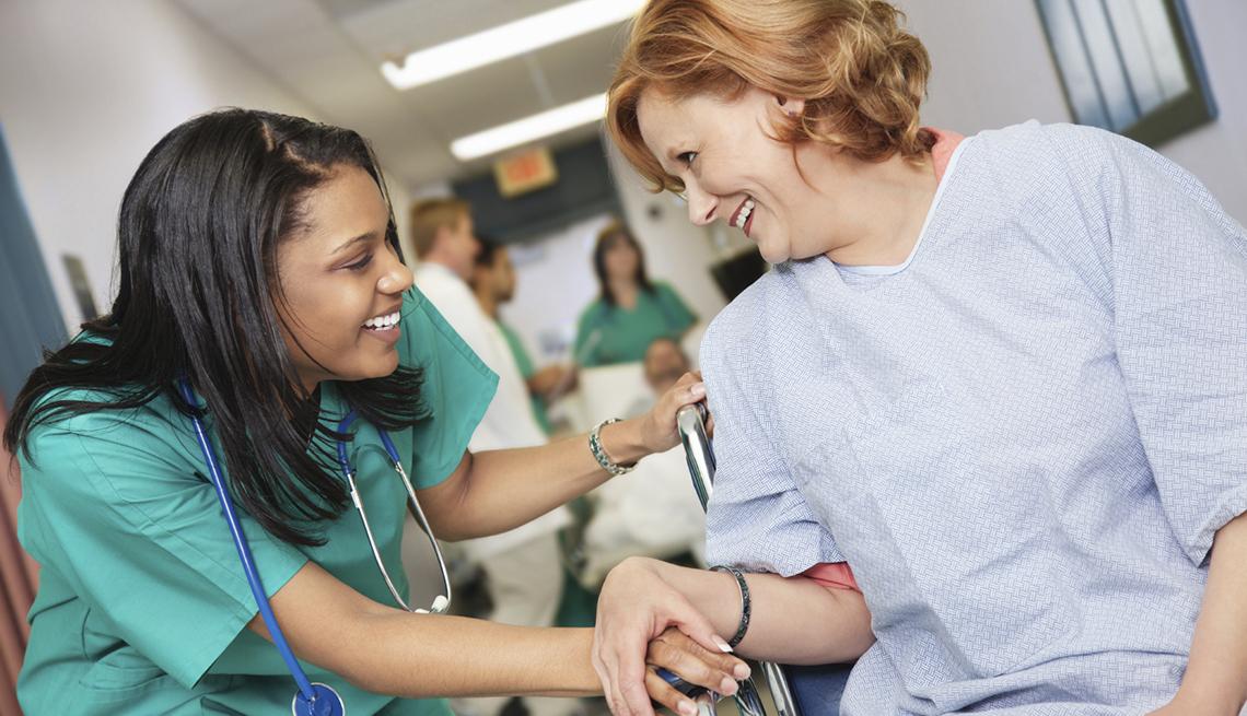 Enfermera afro-americana sonríe junto a una paciente sentada en silla de ruedas en un pasillo de hospital.