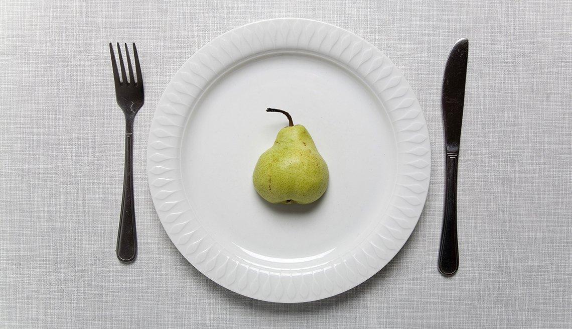 Mitad de una pera en el centro de un plato, cuchillo colocado a la derecha de la mesa y tenedor colocado a la izquierda.