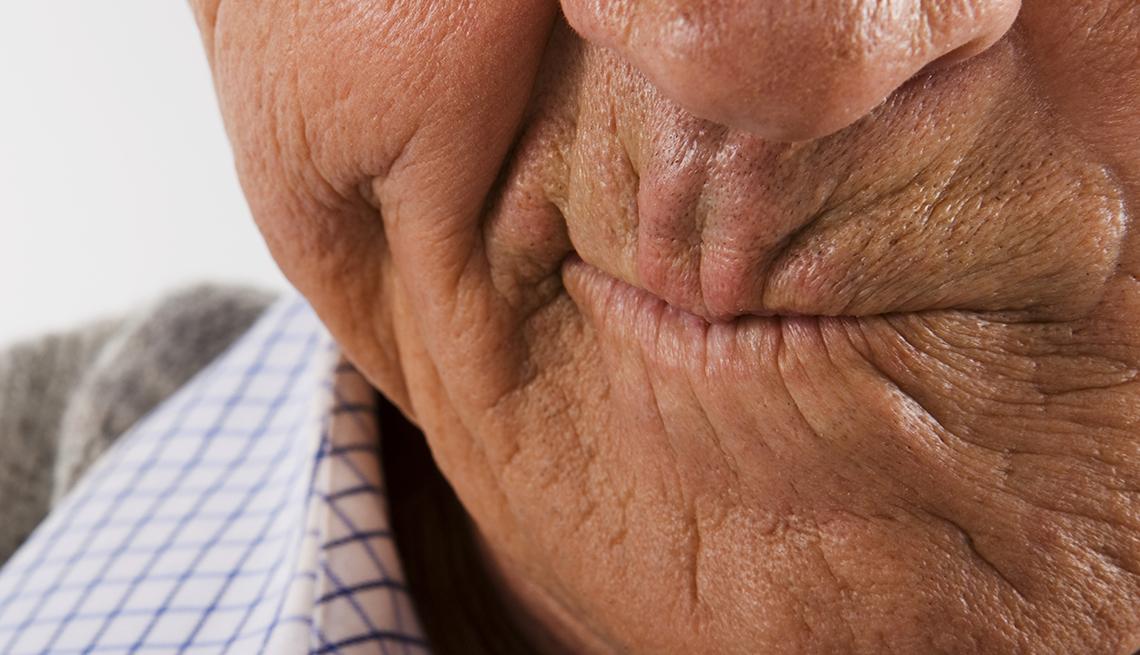 Un hombre mayor hace una mueca de frustración.