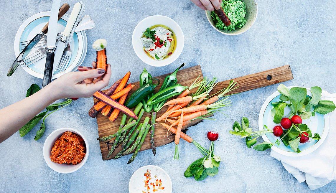 Una mujer toma una zanahoria en la mano de una tabla de vegetales.