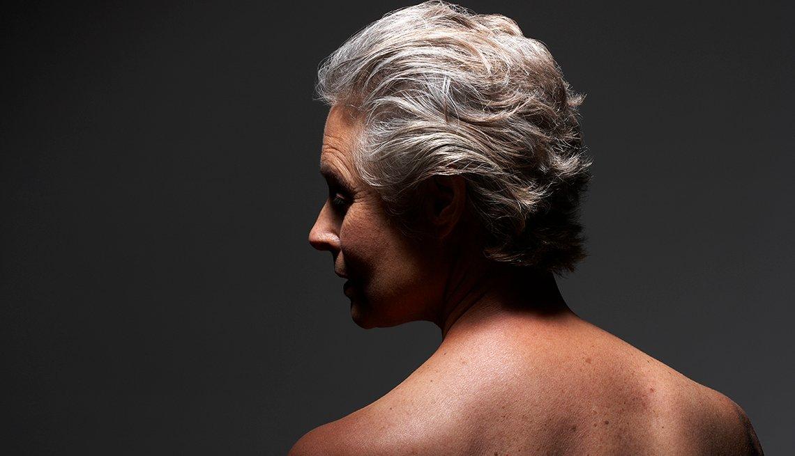 Mujer de mediana edad posa de perfil, cabello con canas.