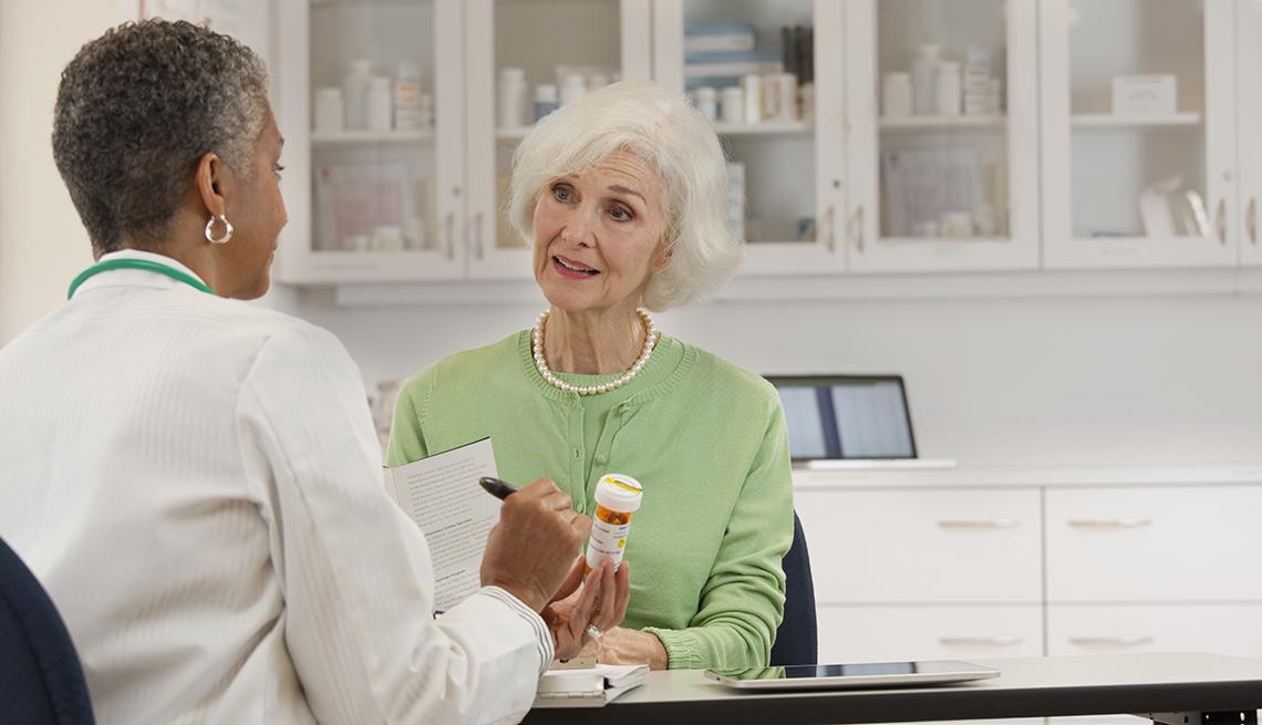 Mujer de la tercera edad con frasco de medicina en la mano pregunta a doctora afro-americana.