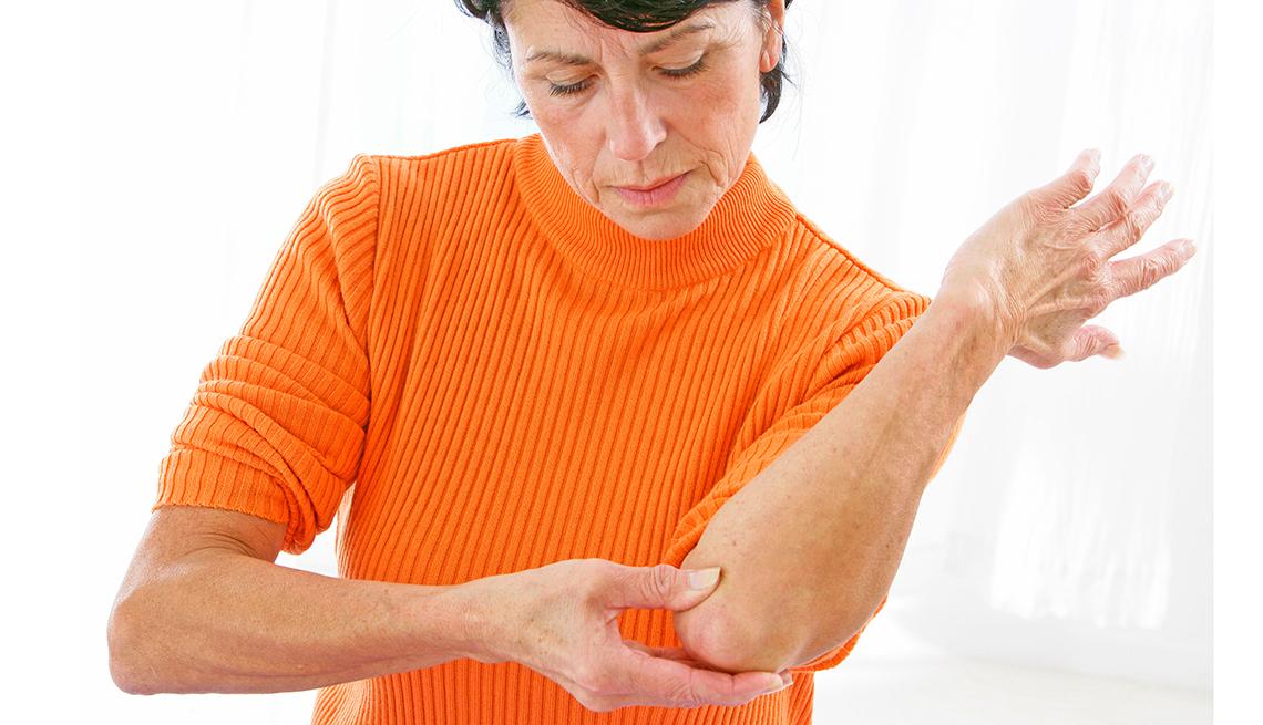 Mujer de mediana edad con un suéter naranja toca su codo izquierdo.