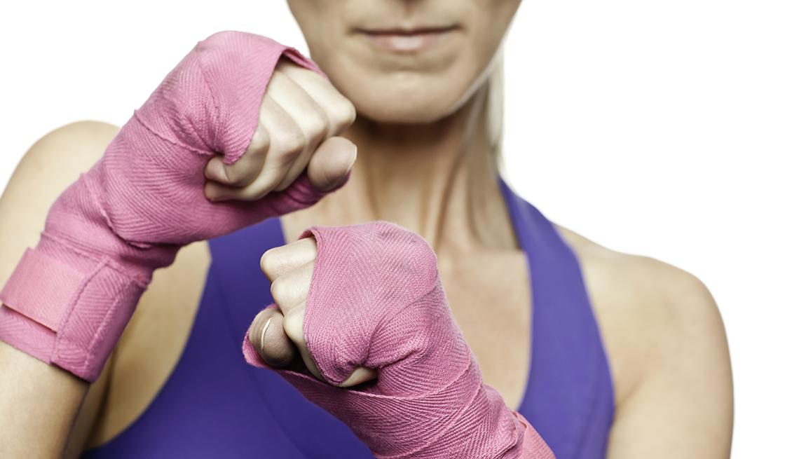 Mujer con guantes en color rosa en posición de boxeo.