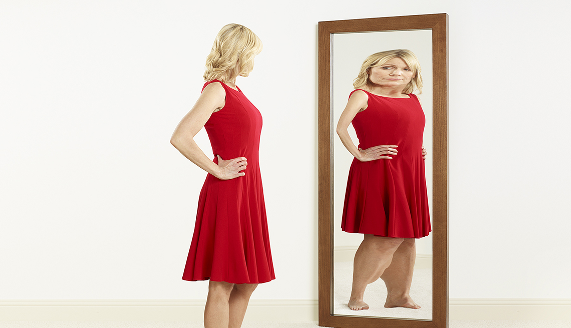 Mujer vestida de rojo ve el reflejo de su imagen deformada en un espejo.