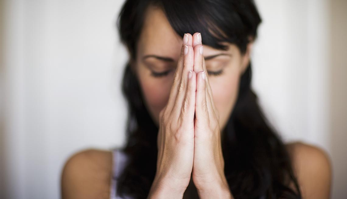 Mujer de pelo negro con las manos en posición de meditación o rezo.