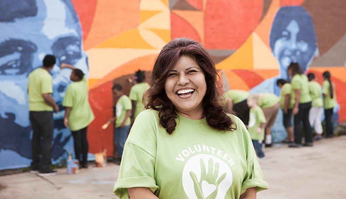 Mujer hispana sonríe con una camiseta que dice voluntaria.