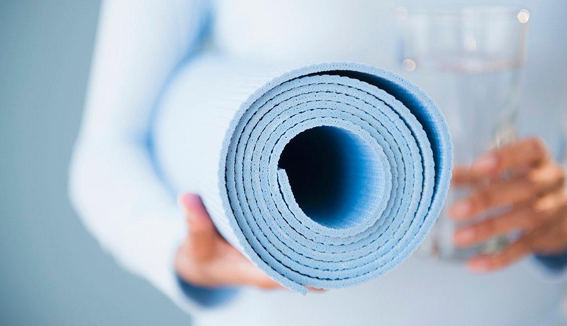 Mujer sostiene un tapete de yoga en una mano y en la otra un vaso de agua.