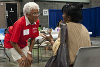 volunteer helps patient at free health clinic