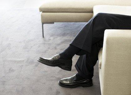 Un hombre sentado en un sofá con las piernas cruzadas