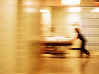 Nurse rushing a patient on a stretcher down a hallway. How to avoid hospital readmission.