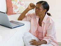 women at computer in bedroom