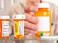 Man taking prescription out of medicine cabinet