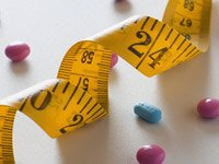 Pastillas diseminadas alrededor de una cinta métrica. Algunos medicamentos pueden hacer que aumente de peso.