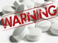 Pastillas en blanco con un letrero de cuidado - Analgésicos comunes pueden causar otros problemas de salud si se utilizan mal
