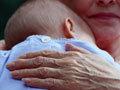 Grandmother with Baby laying on her chest and arm