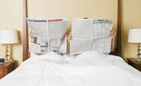 couple in bed reading newspaper - 7 Meds That Can Wreck Your Sex Life