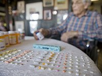 Mature man sitting with table of multiple prescribed medications